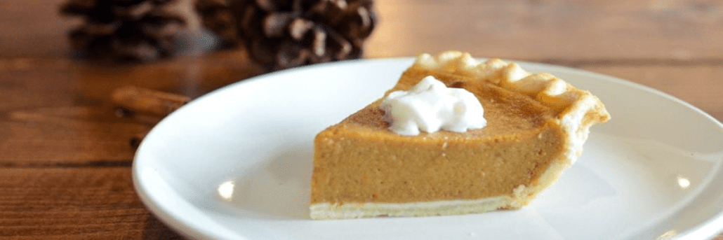 Slice of pumpkin pie on a white plate on a wooden table. Gratitude for Wellness. As we approach another Thanksgiving, we want to take a moment to reflect on the past year and all the changes that came with it.